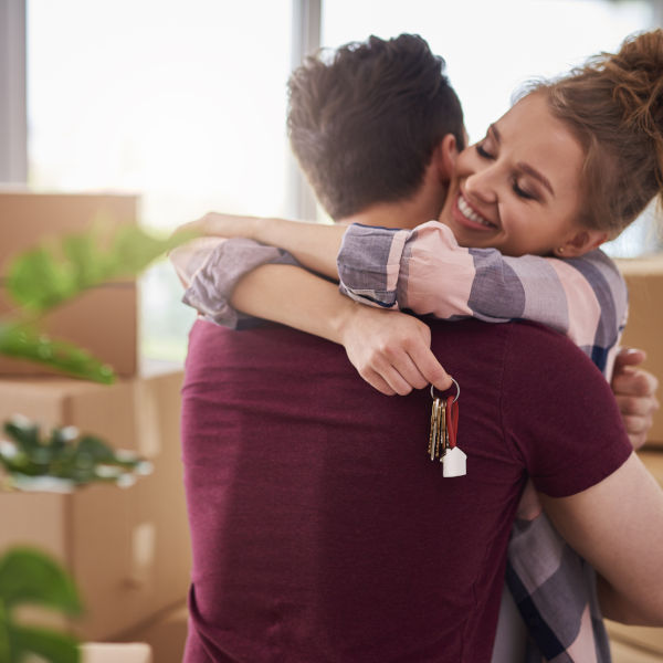 Young couple embracing while holding keys to new home
